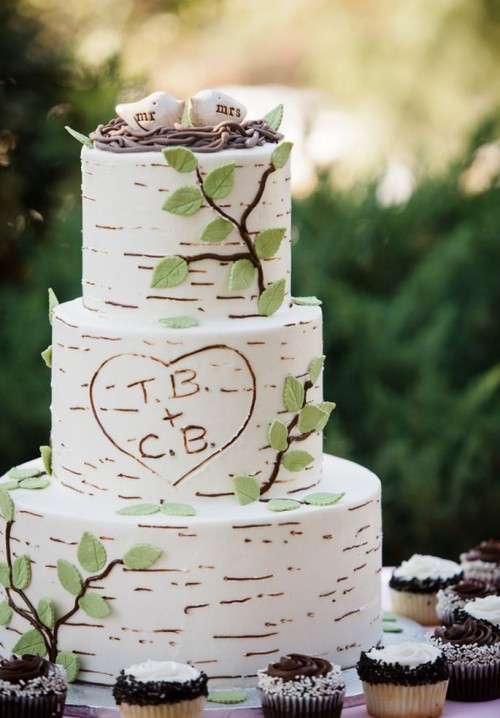 a cute woodland wedding cake that seems to be covered with birch bark, fake branches and a faux nest with birdies on top