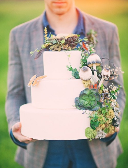 a pure white wedding cake topped with moss, succulents, faux mushrooms, a butterfly and even a faux nest on top