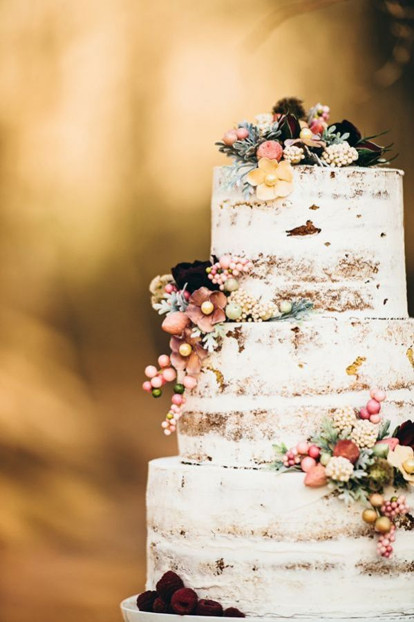 a semi naked wedding cake topped with blooms and berries is a very relaxed and rustic like idea