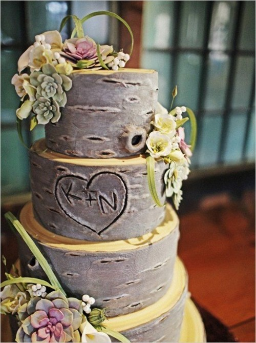 a bark wedding cake with neutrals, fake succulents, greenery and blooms for a woodland wedding