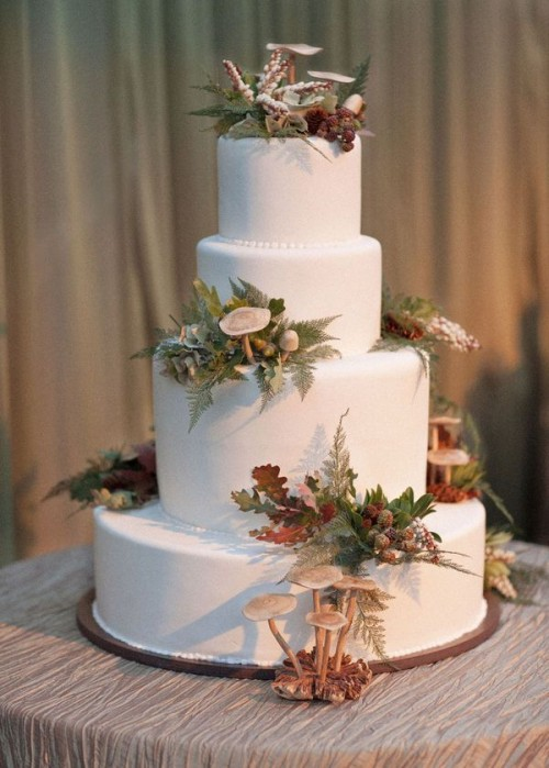 a pure white wedding cake topped with mushrooms, ferns, foliage and berries that are all edible