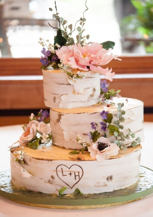 a woodland wedding cake that seems to be made of birch slices, with sugar flowers and greenery
