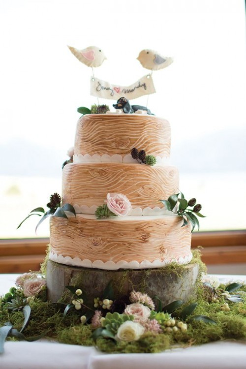 a woodland wedding cake that imitates wood, with fresh blooms and greenery and a bird topper with a banner