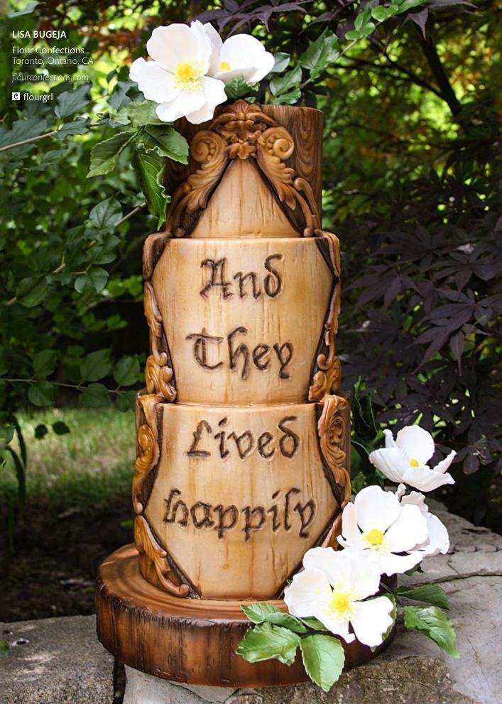 a fantasy woodland wedding cake that seems to be carvedout of wood, with a fake burnt inscription and sugar blooms on top