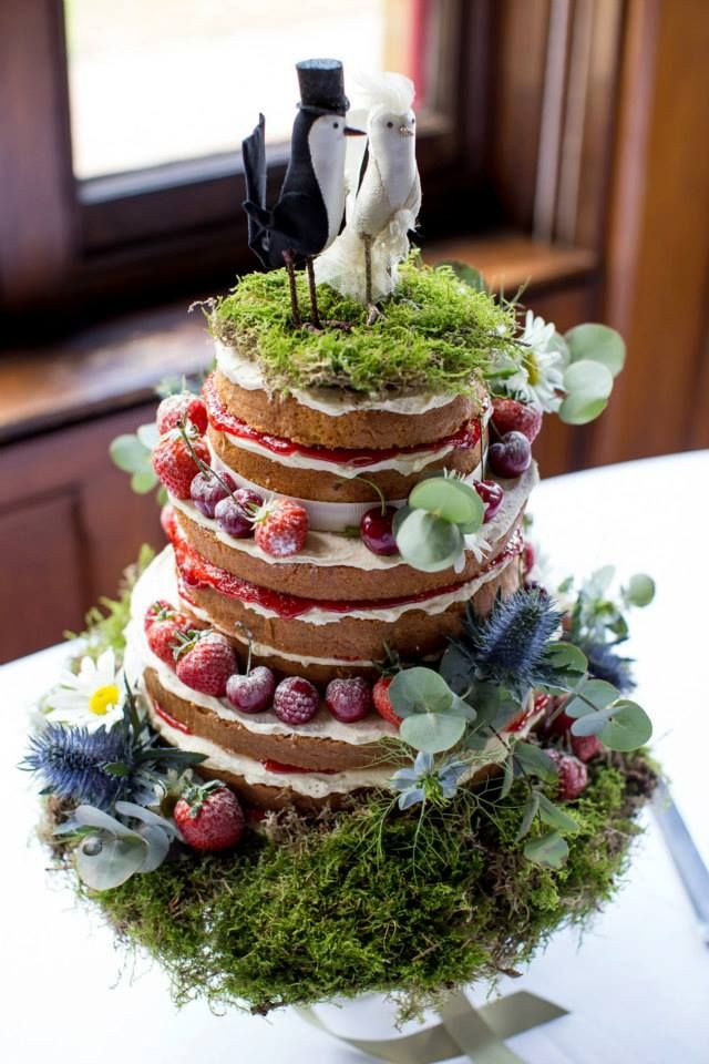 a summer woodland naked wedding cake with fresh berries, moss, greenery, bird toppers on a moss pillow with greenery