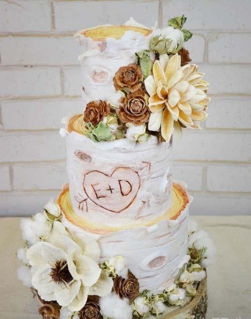 a rustic wedding cake with bark, sugar and real blooms, cotton, greenery