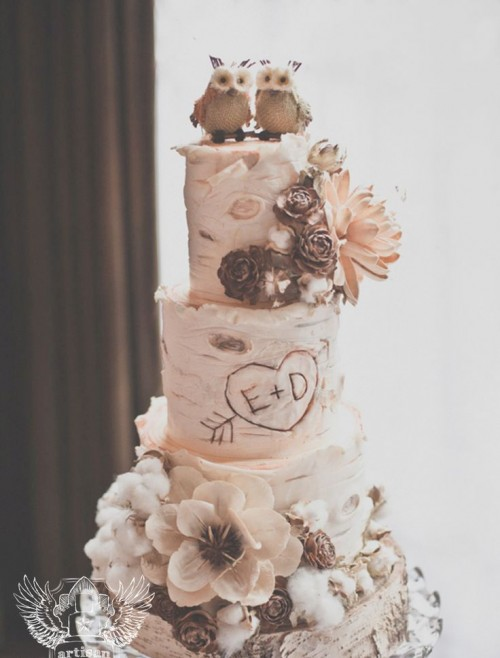 a cozy rustic wedding cake that looks like it's covered with birch bark, cotton, faux blooms, berries, pinecones and with fun owl toppers