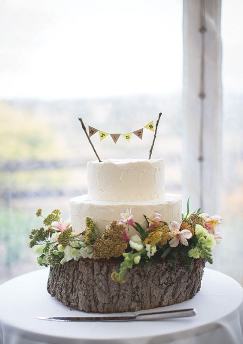 a white textural buttercream wedding cake topped with a banner, on a wood slice with greenery and blooms