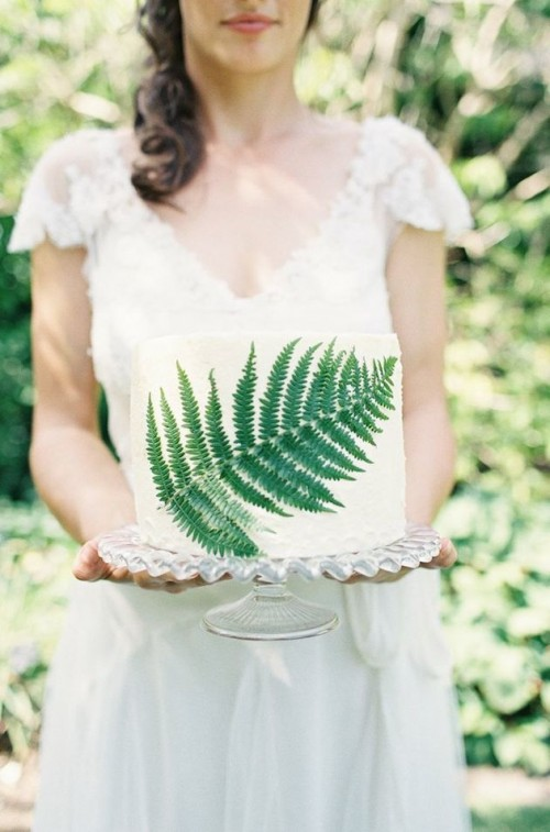 a simple woodland wedding cake in white with a pressed fern leaf for decor is a cute and fresh idea