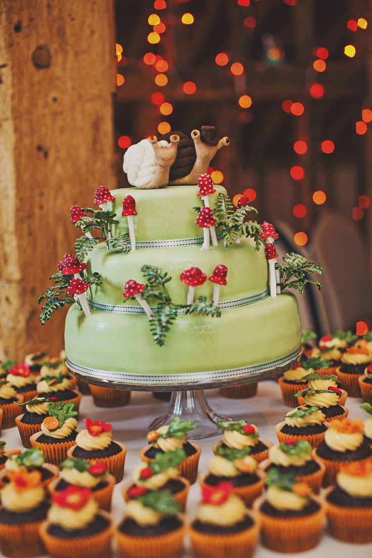 a fun woodland wedding cake in green, with sugar foliage and mushrooms plus funny snail toppers