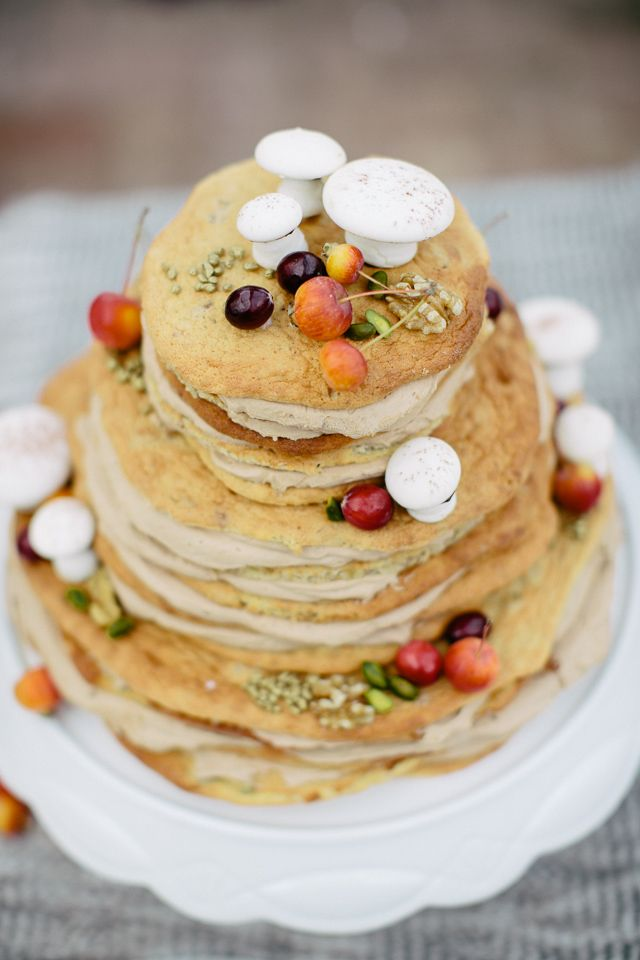 a naked wedding cake topped with blooms, berries and sugar mushrooms on top looks super natural and real