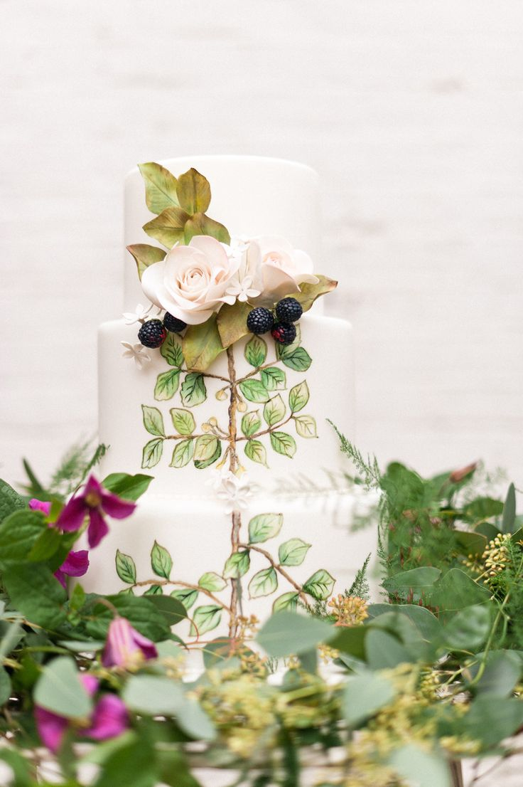 a beautiful handpainted wedding cake with dried foliage, blooms and some fresh berries