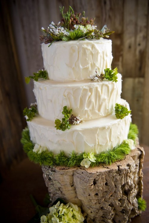 a cozy rustic woodland wedding cake with textural buttercream, moss, grass, berries and served on a wood slice