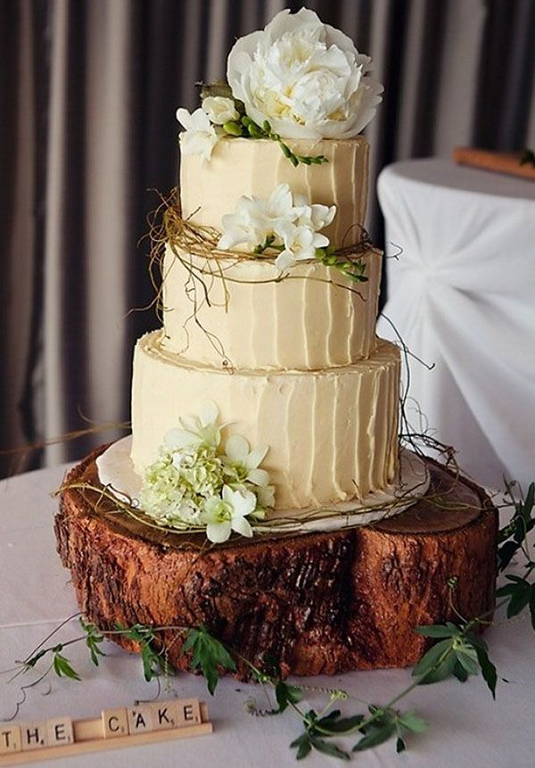 a rustic wedding cake with neutral textural buttercream, greenery, moss, white blooms and served on a wood slice