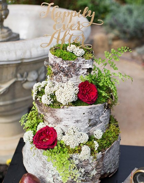 a unique woodland wedding cake that seems to be made of bark, moss and decorated with fresh blooms plus an elegant topper