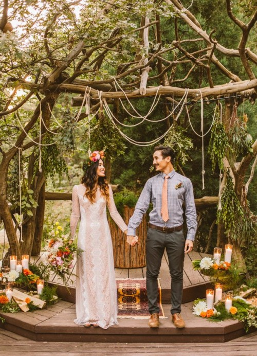 a boho lace sheath wedding dress with a sheer neckline, long sleeves and a bright floral crown