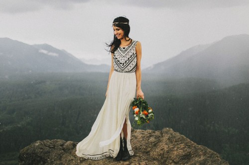 a folksy wedding dress with no sleeves and an A-line skirt with a slit plus blakc embroidery, black boots and a boho headpiece