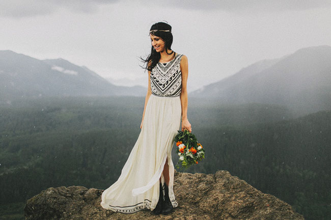 a folksy wedding dress with no sleeves and an A line skirt with a slit plus blakc embroidery, black boots and a boho headpiece
