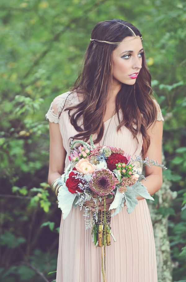 a blush sheath wedding gown with embellished cap sleeves, a V neckline and a boho chain on the head