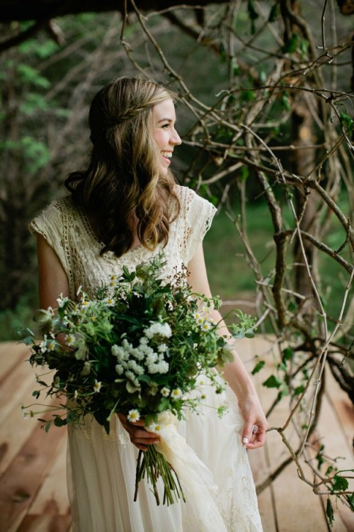 a relaxed boho lace cap sleeve wedding dress with a scoop neckline and a bouquet of wildflowers