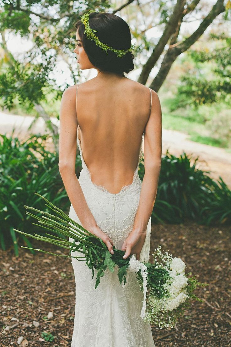 a sexy lace sheath wedding dress with spaghetti straps and an open back plus a greenery crown