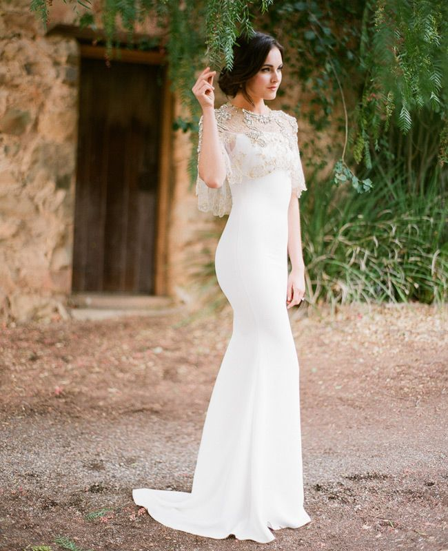 an elegant white mermaid wedding dress with spaghetti straps and an embellished coverup