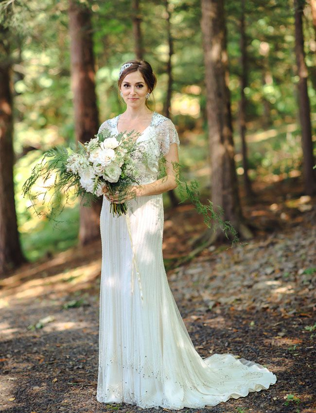 an art deco embellished wedding dress with a train and a V neckline plus cap sleeves