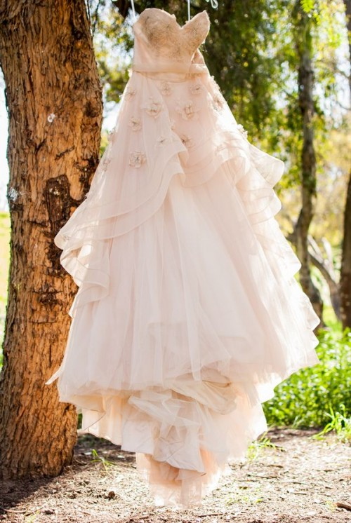 a girlish blush A-line wedding dress with a full skirt, with an embroidered bodice and fabric flowers on the skirt