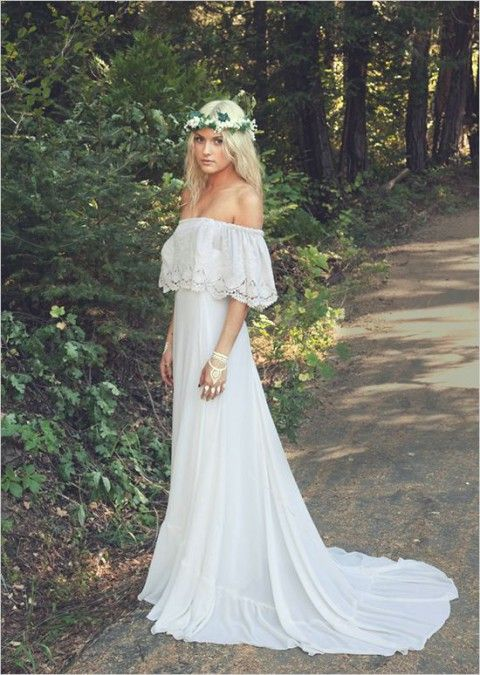 a boho off the shoulder wedding dress with a lace neckline and a train plus a floral crown