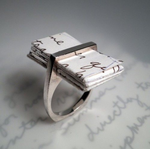 an engagement ring with a sleek line and a love letter inserted inside it is a very modern and very romantic solution
