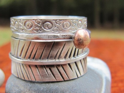 a beautiful silver engagement ring with feather detailing and patterns, a large ball is a lovely idea for a boho or folksy couple
