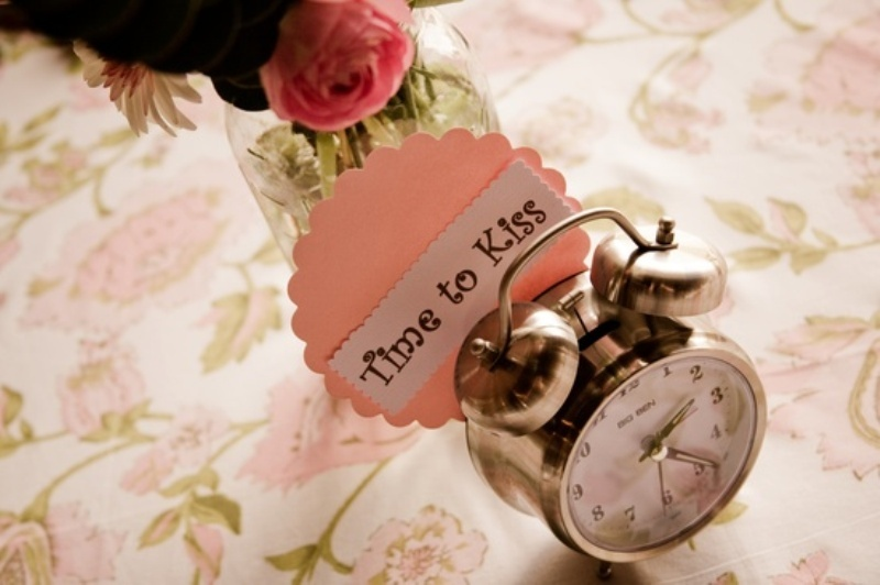 a clock with a funny tag is a cool decoration for a wedding table, pair it with blooms and greenery