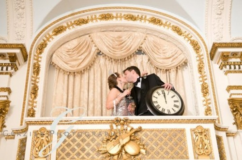 the couple kissing and holding a clock is a pretty and cool wedding portrait idea for a NYE wedding