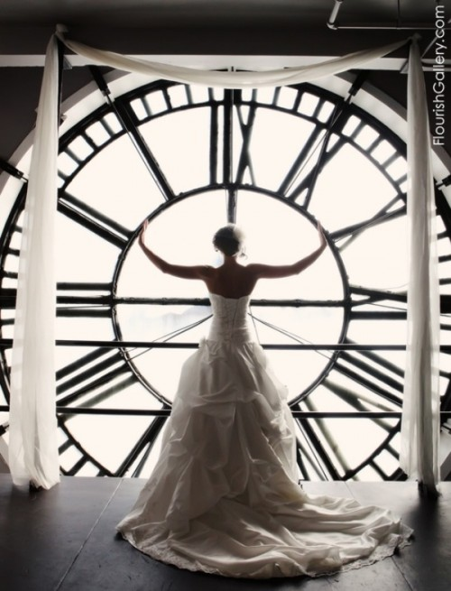 show off your wedding dress in front of a window with a giant clock, it will be a memorable and bold picture