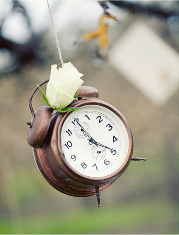 a vintage clock with a white bloom attached is a cool idea for a vintage wedding