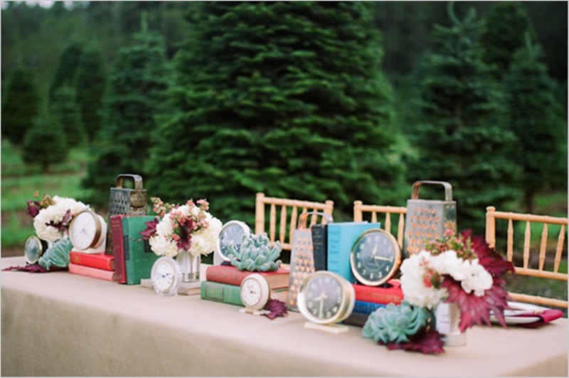 a vintage wedding table decorated with colorful books, clocks, blooms and succulents