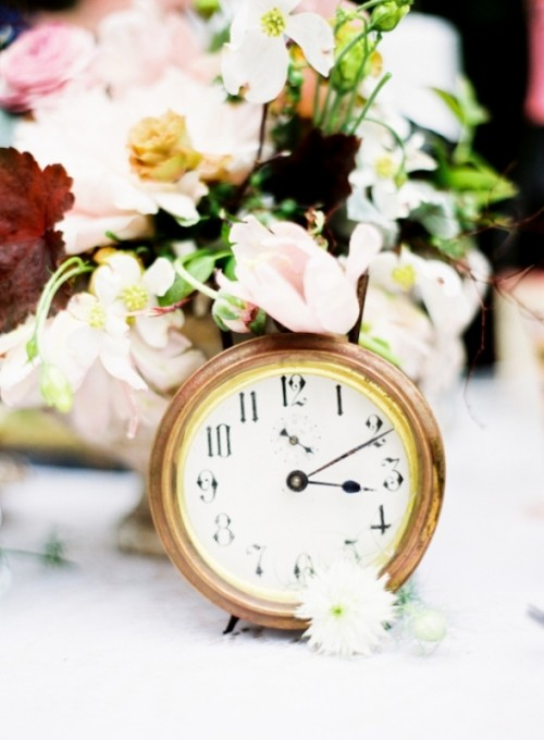a pastel bloom wedding centerpiece with a clock is a pretty idea for a celestial, NYE or vintage wedding