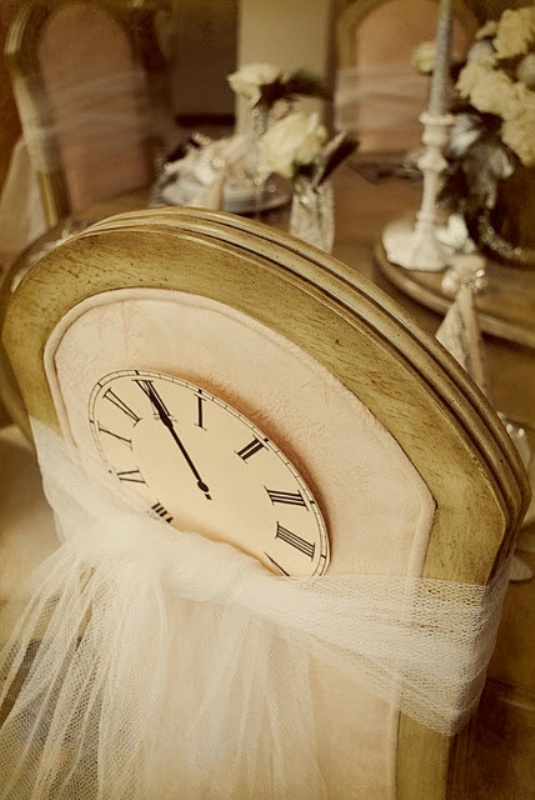 a cardboard clock attached to the chair with tulle is a fun decoration idea for a NYE wedding
