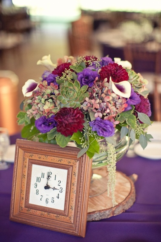 a colorful wedding centerpiece of bright blooms and a clock in a frame for a whimsy vintage wedding reception table