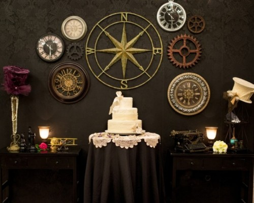 a white wedding cake displayed in front of a wall decorated with large gears and clocks is a cool idea