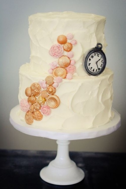 a textural white buttercream wedding cake decorated with pink and gold detailing and an edible clock for fun