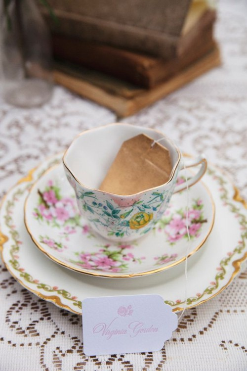 a refined floral teacup with a saucepan with a teabag escort card is a lovely idea for a brunch wedding