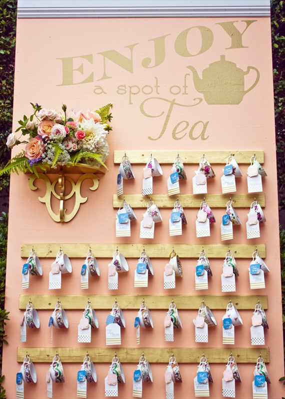 a blush wall with wooden holders, lush florals and vintage teacups with tags and escort cards