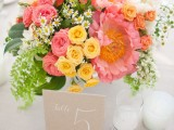 a bright summer wedding centerpiece of coral pink, orange, yellow and white blooms and greenery is a vivacious summer decoration