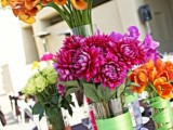 super bold summer wedding centerpieces of vases wrapped with ribbon and with fuchsia, orange, green blooms of various kinds