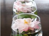 a clear jar with a single blush bloom floating in it will save your flower budget and will add a soft summer feel to the tablescape