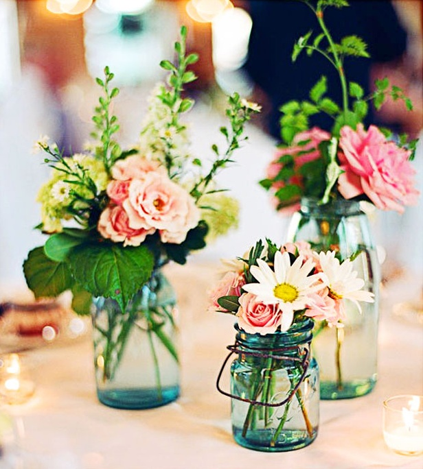 pretty summer wedding centerpieces of blue jars, with pink and neutral blooms and greenery look delicate and romantic