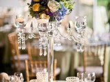 a refined summer wedding centerpiece of a crystal candelabra with candles and bright blooms and greenery and with candles in crystal candleholders