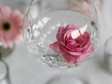 a clear glass with pearls and a pink rose is a budget-friendly and very refined summer wedding centerpiece
