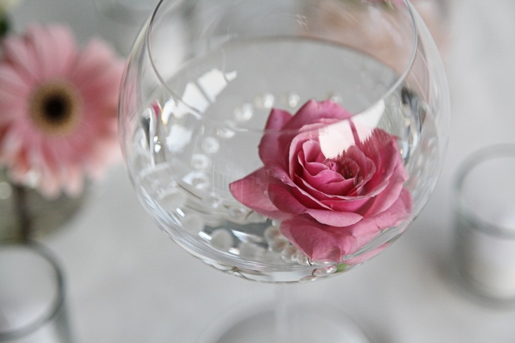a clear glass with pearls and a pink rose is a budget friendly and very refined summer wedding centerpiece